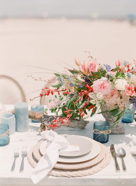 a bold beach bridal shower table with blue candles and candleholders, bright blooms and rope placemats