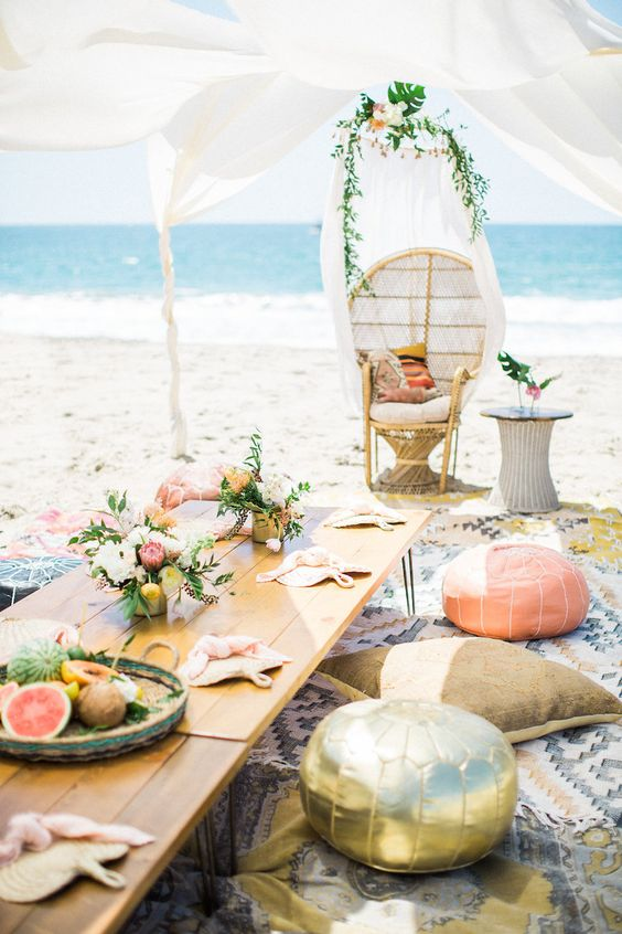 a bright beach bridal shower setting with colorful pillows and ottomans, with bright blooms and citrus in a plate