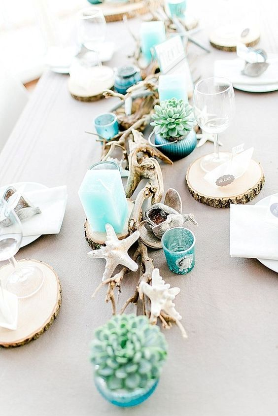 a bright beach bridal shower table with driftwood, candles, blue candleholders, succulents, starfish and wood slices