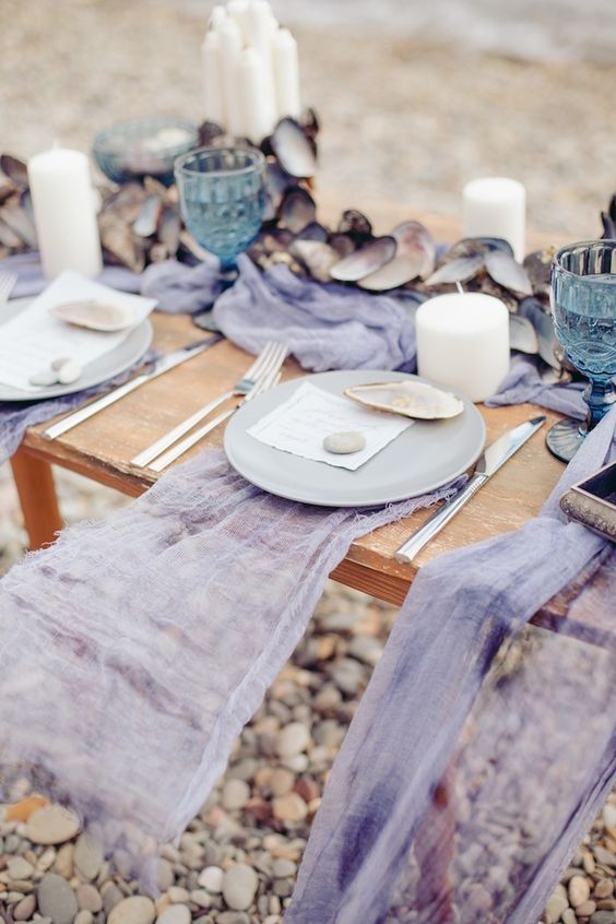 a bright beach bridal shower table with lavender linens, blue glasses, candles and seashells looks unusual
