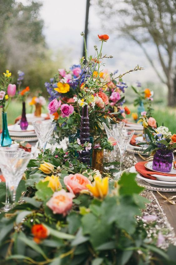 a bright boho garden bridal shower tablescape with super colorful blooms and textural greenery, bright vases and arrangements