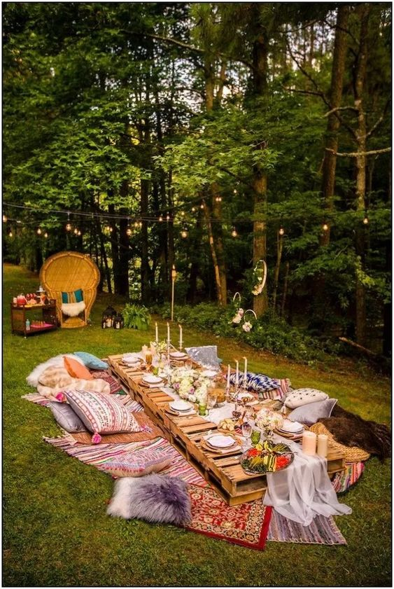 a bright boho summer wedding picnic with colorful rugs, pillows, a pallet table, thin candles and an airy runner