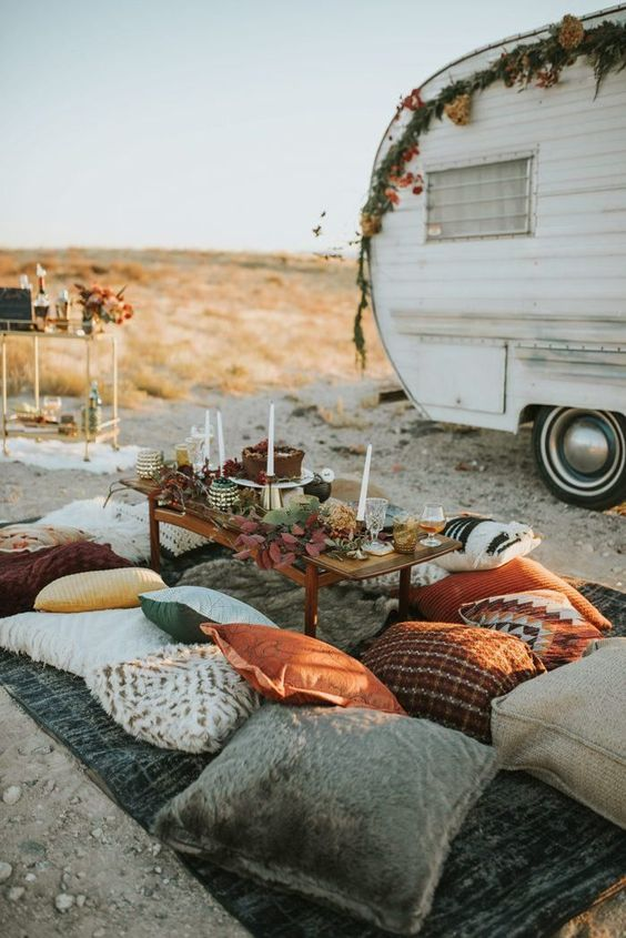 a bright boho wedding picnic with a dark blanket, bright pillows, a low table, candles and dark foliage