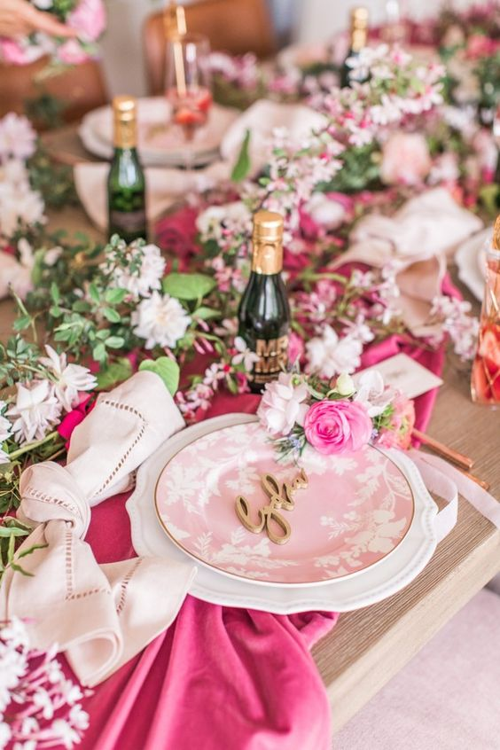 a bright bridal shower tablescape with a greenery and white bloom garland, with bold pink linens, a pink floral plate and neutral cards