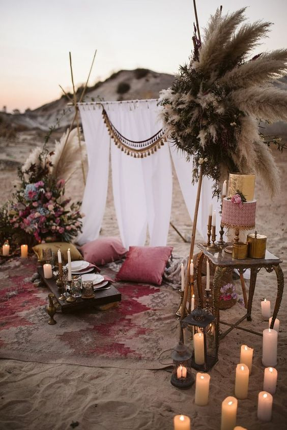 a bright desert boho picnic with a neutral backdrop with pompoms, colorful pillows, lots of candles, pampas grass and blooms