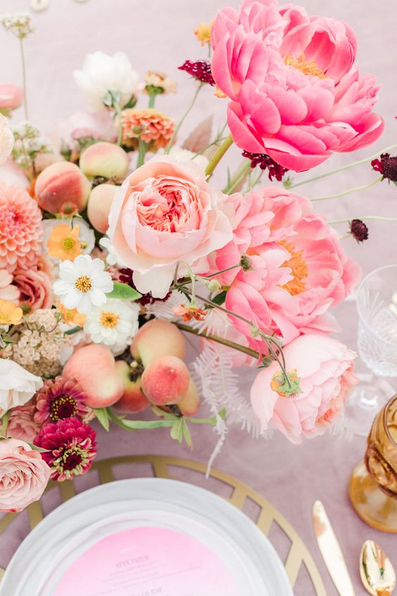 a bright garden bridal shower tablescape with a pink tablecloth and a menu, with bright pink and neutral blooms and fruits is wow
