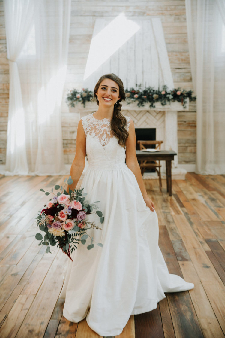 a chic and romantic barn wedding dress with no sleeves, a lace bodice and a full skirt with a train