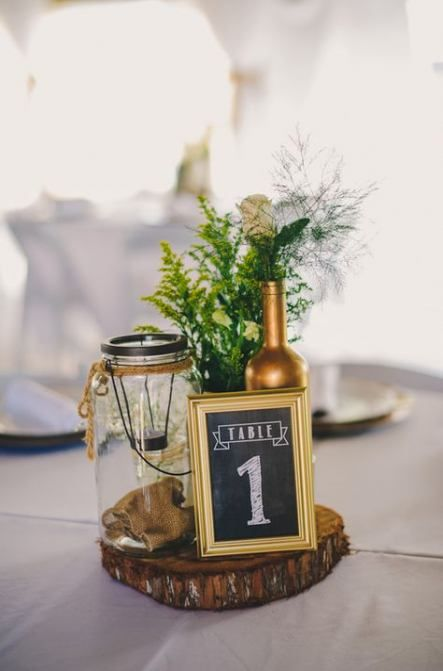 a chic and simpel barn wedding centerpiece of a wood slice, a table number, greenery and neutral blooms, a gilded bottles and a candle lantern