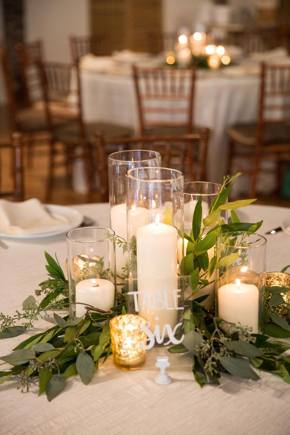 a chic and simple barn wedding centerpiece of foliage, candles in tall glasses and mercury glass candleholders