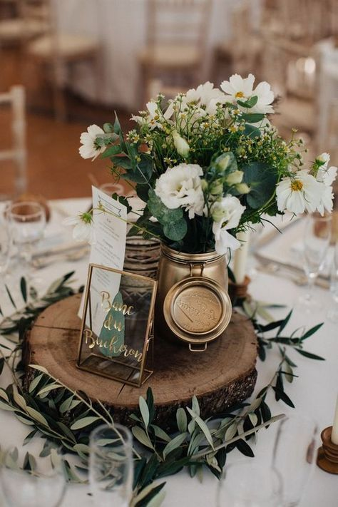 a chic barn wedding centerpiece of a wood slice, greenery, a gilded jar with neutral blooms and greenery and a metallic table name