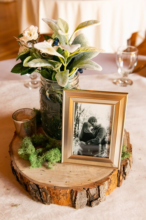 a chic barn wedding centerpiece of a wood slice, moss, some greenery and neutral blooms plus the couple's photo