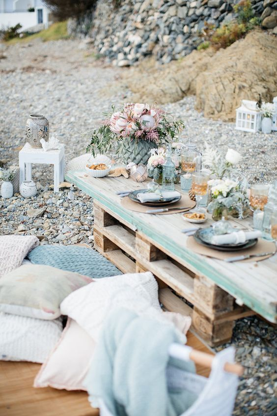a chic coastal bridal shower picnic with a pallet table, lots of pillows, pastel blooms, gold glasses and blue plates plus greenery