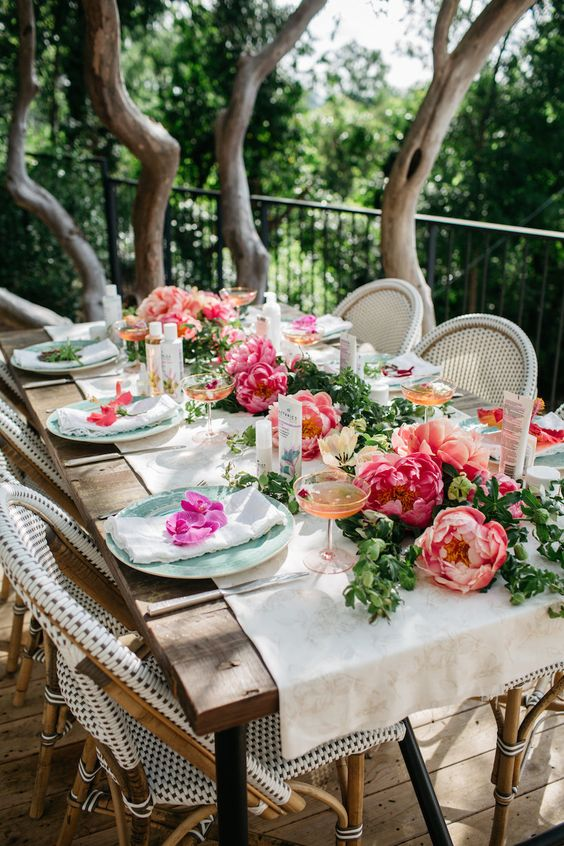 a chic garden bridal shower table with a bold floral and greenery table runner, colored glasses and pastel plates