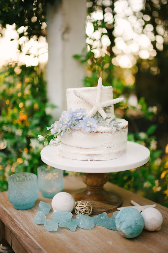 a chic naked beach bridal shower cake with blue blooms and starfish, surrounded with seaglass and blue candleholders
