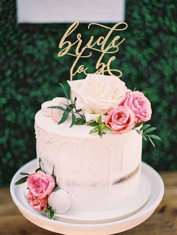 a chic naked wedding cake with white drip, white and pink blooms and a gold calligraphy topper is amazing