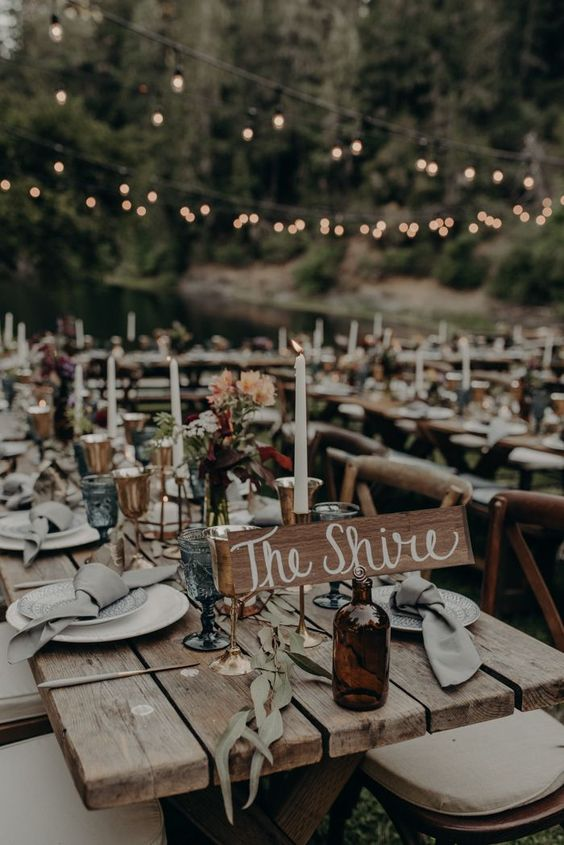 a chic outdoor barn wedding reception space with uncovered tables, pastel blooms and greenery, elegant candles and neutral linens