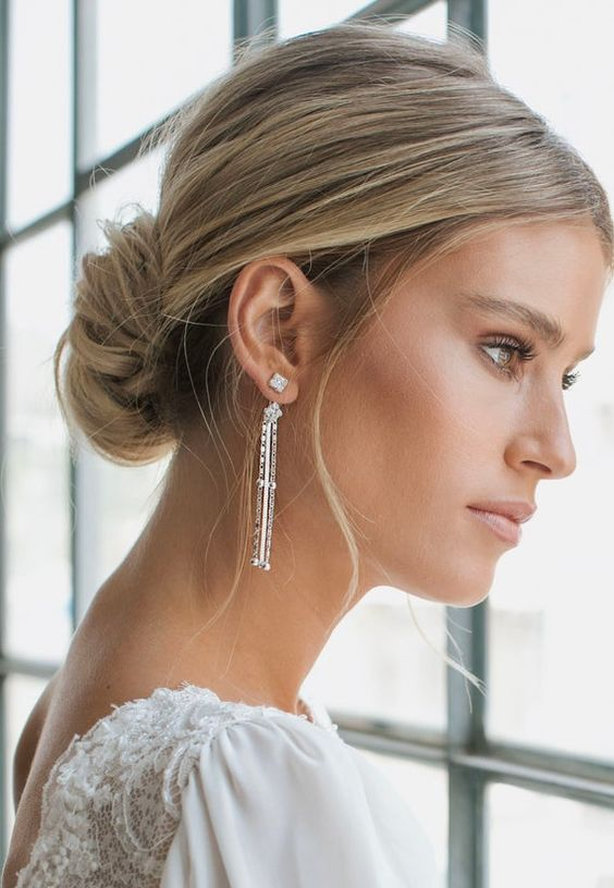 a classic low chignon with a volume on top and some locks down is a beautiful and cool hairstyle for a modern refined bride