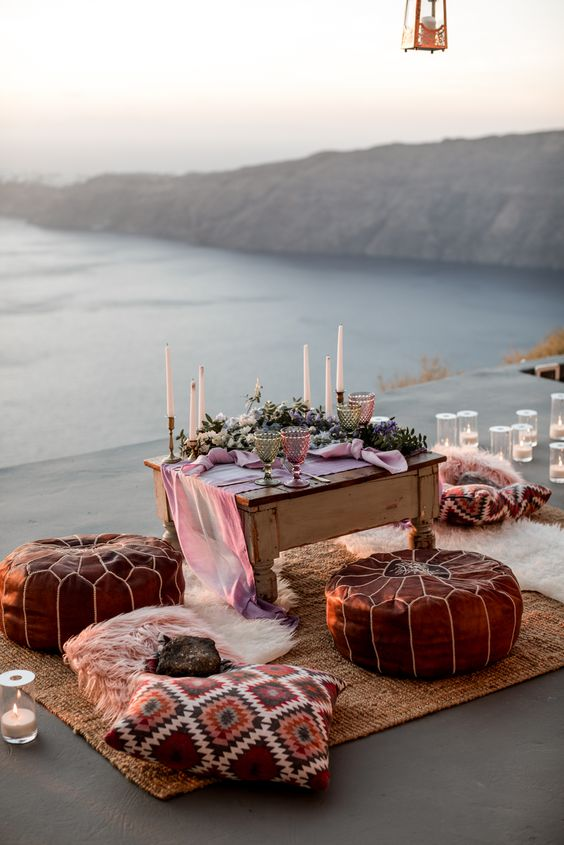 a coastal wedding picnic with a biew, leather ottomans, bright pillows, pink candles and napkins plus greenery