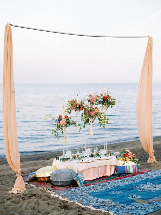 a colorful beach bridal shower picnic setting with bold blooms and textiles, colorful glasses, candleholders