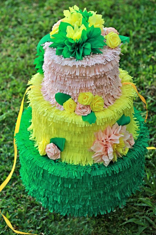 a colorful cake-shaped pinata wedding guest book topped and decorated with bright paper blooms and leaves is a very fun and bright idea