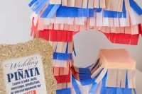 a colorful monogram pinata wedding guest book with fringe is a very cool and fun idea for a modern romantic wedding