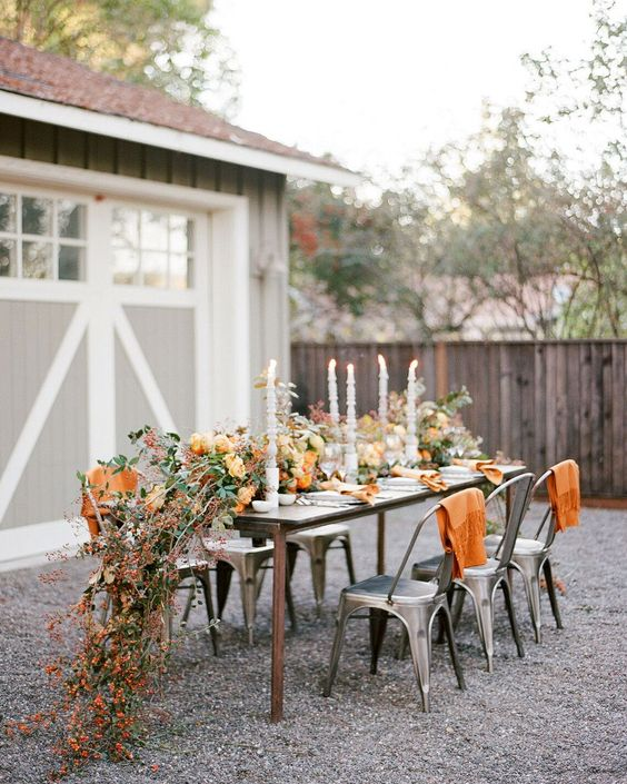 a cool fall outdoor barn wedding reception with a lush table runner of dried foliage and blooms and fruit, elegant candles and orange blankets