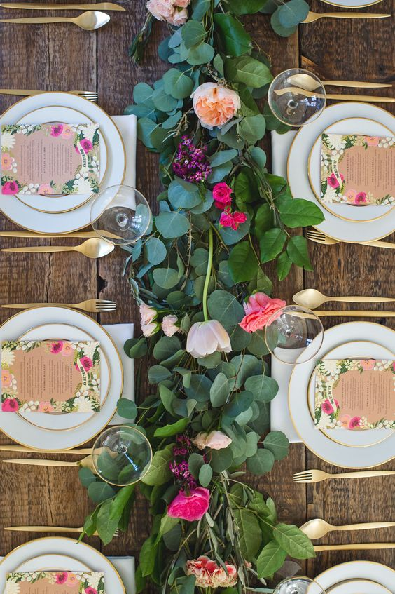 a cool garden bridal shower tablescape with a greenery and bold bloom table runner, floral menus and gold cutlery is cool
