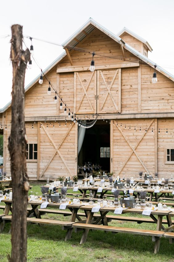 a cool outdoor barn wedding reception space with long tables and benches, with string lights over the space and white linens is welcoming