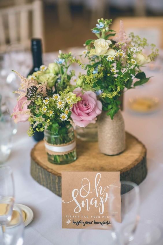 a cozy barn wedding centerpiece of a wood slice, a vase wrapped with twine, jars with lace and wildflowers