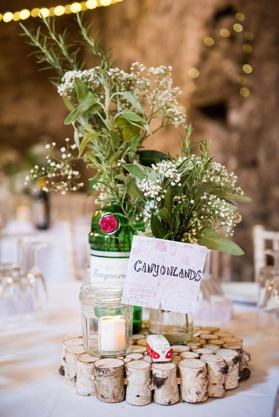 a cozy barn wedding centerpiece of sticks, candles, neutral blooms and greenery and a table name is great