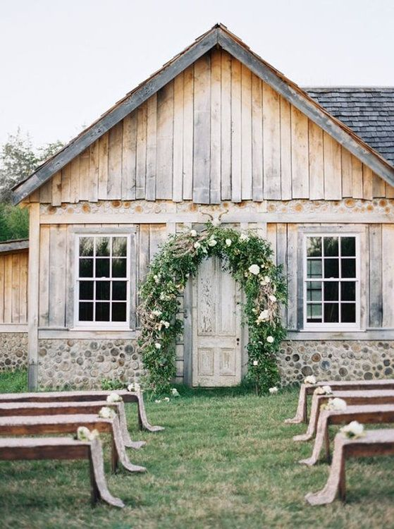 a cozy outdoor barn wedding ceremony space with a greenery and floral arch, some benches with florals and fabric covers