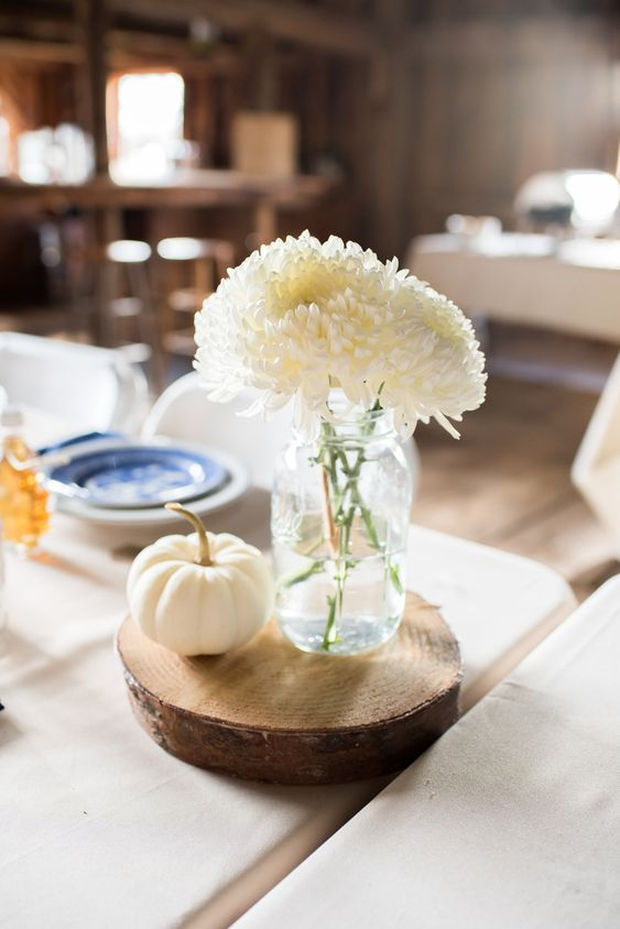 a cute barn wedding centerpiece of a wood slice, a white pumpkin and some white blooms in a jar