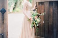 a cute blush wedding gown with a lace bodice and long sleeves and a draped skirt for an ethereal romantic look