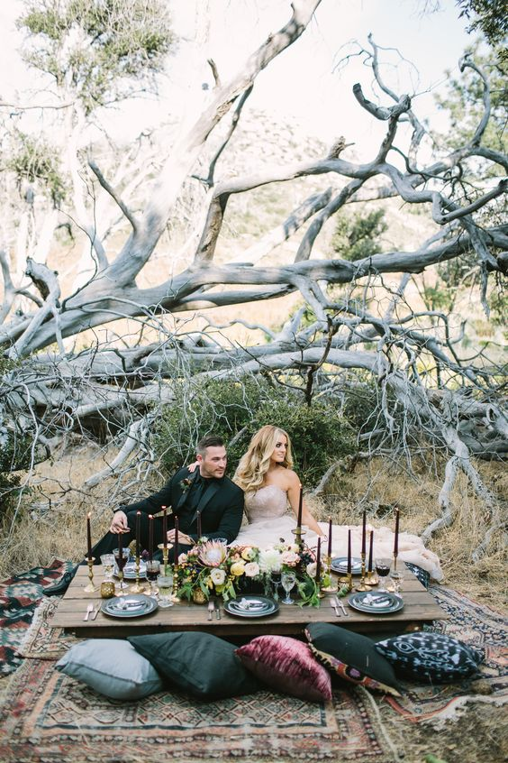 a dramatic Halloween wedding picnic with a low table, dark and jewel pillows, black candles and lush neutral blooms
