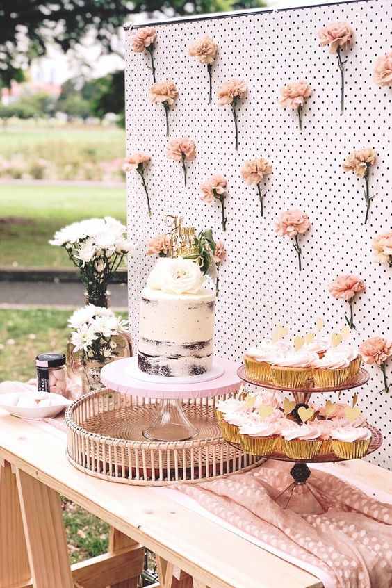 a garden bridal shower sweets table with a blush floral wall, cupcakes and a naked cake is a lovely idea to rock