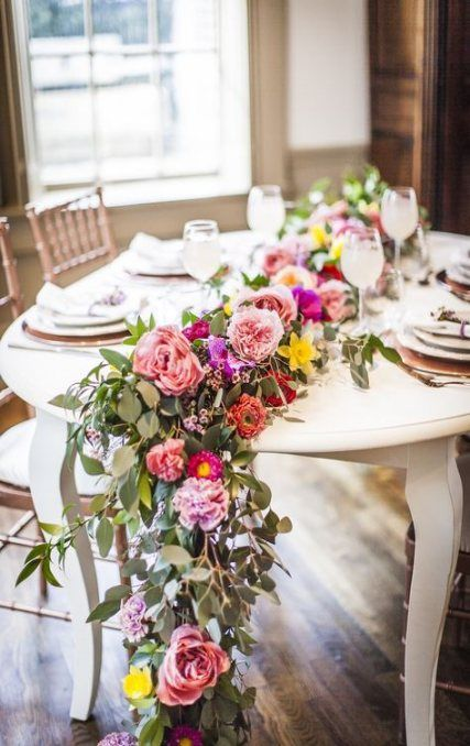 a garden shower tablescape with a lush and bright floral runner and neutral place settings is cool