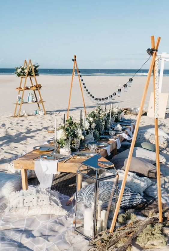 a gorgeous beach bridal shower picnic with a low table, lots of pillows, lights, candles, candle lanterns and greenery