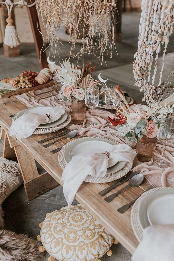 a gorgeous boho beach bridal shower table with pastel blooms, a pink table runner, woven placemats and seashell pendants over the table