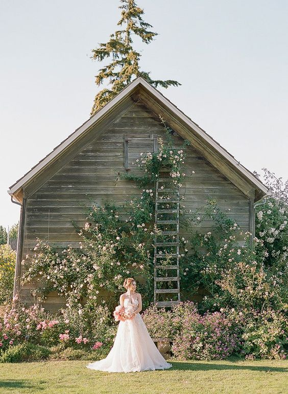 a jaw-dropping outdoor barn wedding ceremony space all covered with greenery and pink blooms is a chic idea to go for