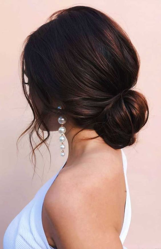a loose low bun with a volume on top and some wavy locks down is a chic and beautiful idea for a modern bride