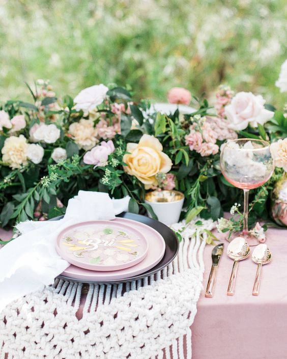 a lovely boho garden bridal shower table with a lush greenery and floral runner, a macrame placemat and gold cutlery plus pink plates