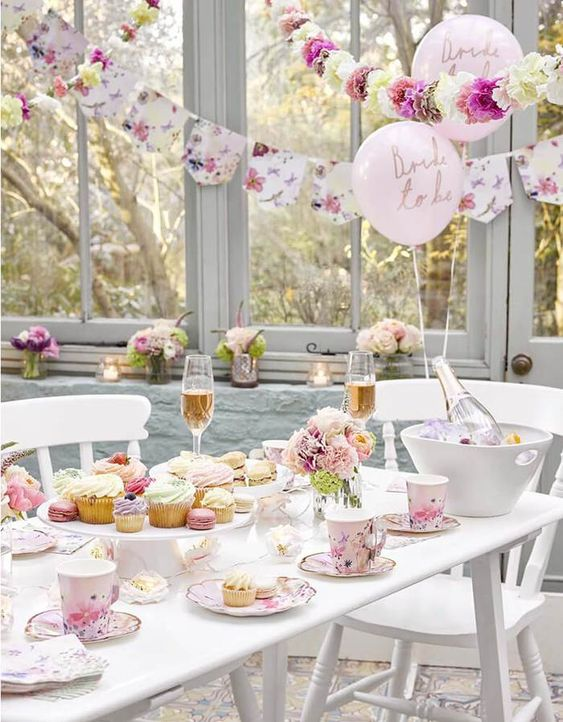 a lovely pastel tea time tablescape with pastel blooms and floral saucepans and teacups, with delicious pastel cupcakes and macarons