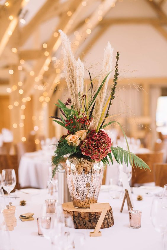 a mercury glass vase on a wood slice, bright blooms, greenery and pampas grass plus berries for a barn wedding