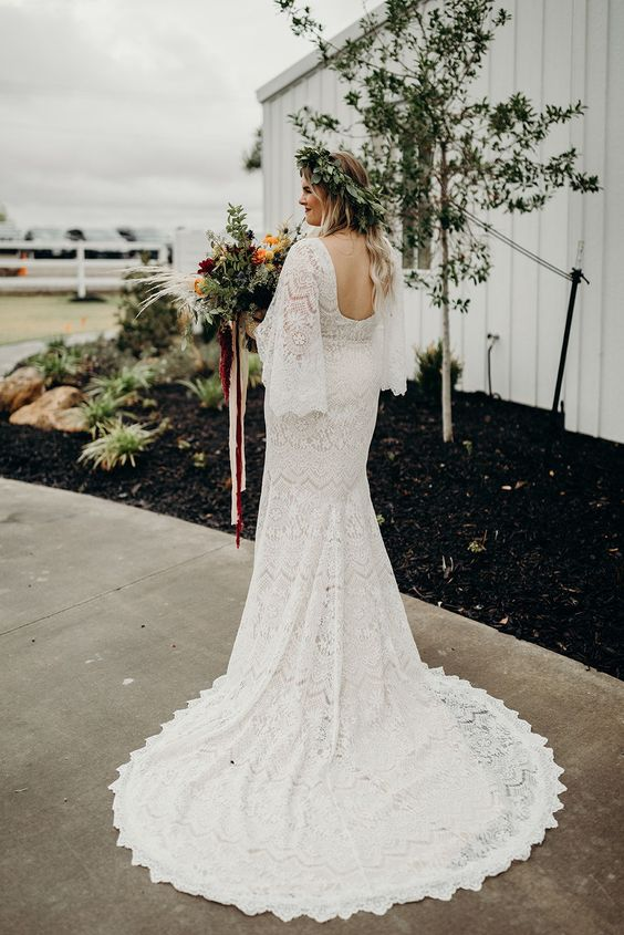 a mermaid boho lace wedding dress with a train, a cutout back and bell sleeves for a boho barn bride