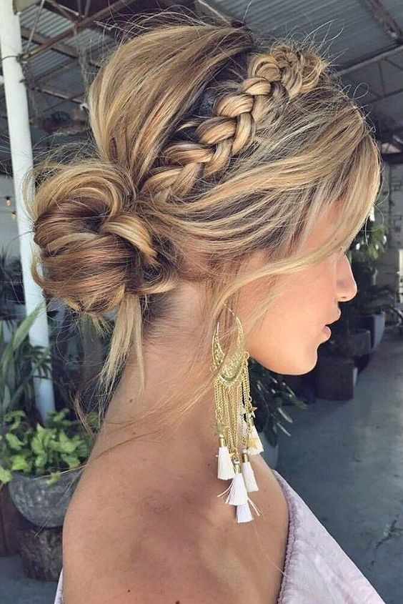 a messy boho low bun with a messy volume on top, a braided halo, some locks down looks very stylish and bold