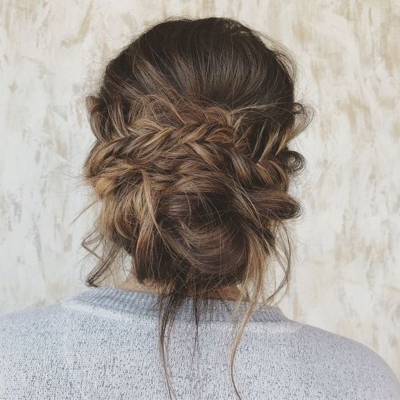 a messy low updo with several braids, a volume on top and some locks down is a great option for a boho bride