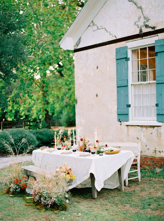 a micro outdoor barn wedding reception space with neutral linens, elegant candles and bold fall florals and greenery plus rustic furniture