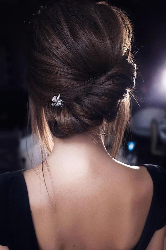 a modern low updo with a twisted low chignon and a voluminous top plus some locks down is a stylish idea