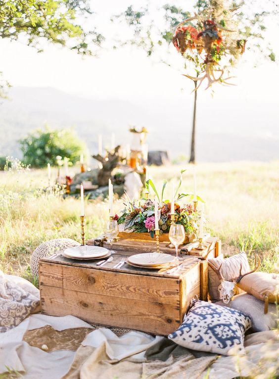 a pallet table, thin candles, bright blooms and greenery, blankets and pillows for a cozy summer picnic wedding
