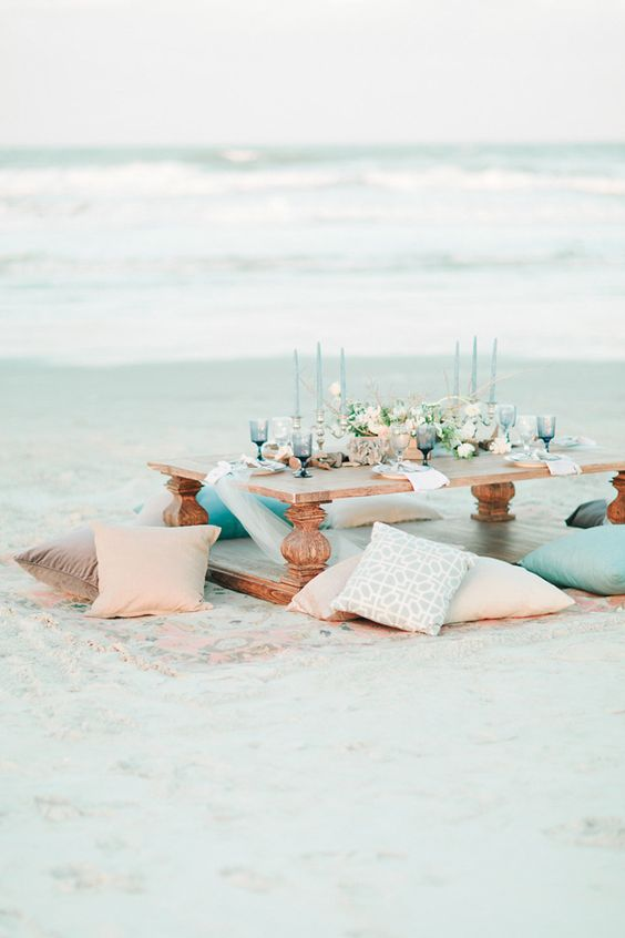 a pastel beach bridal shower with a low table, pastel pillows, blue glasses and candles plus neutral blooms
